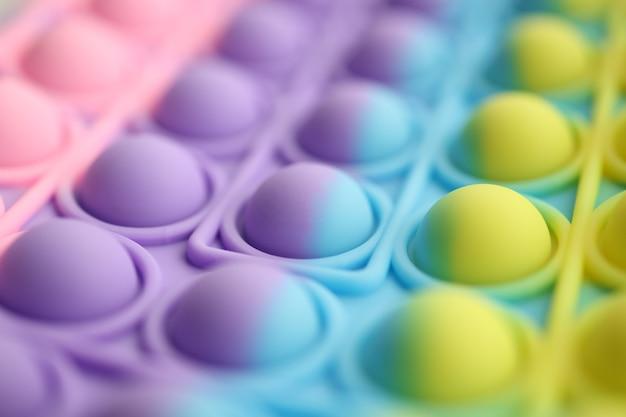 色とりどりのプチプチがテーブルの上に明るい色でポップします無限のプチプチと抗ストレス
