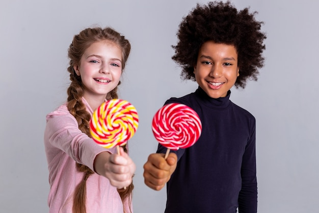 Multicolored candies. pretty good-looking kids staying nearby and posing for photoshoot while wearing turtlenecks