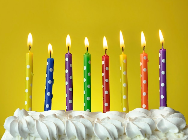 Multicolored candles burn on a birthday cake on a yellow background