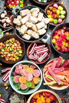 Разноцветные конфеты, желе и зефир в миске. на деревенском фоне.