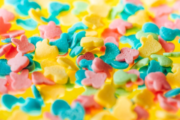 Multicolored candy on a yellow background