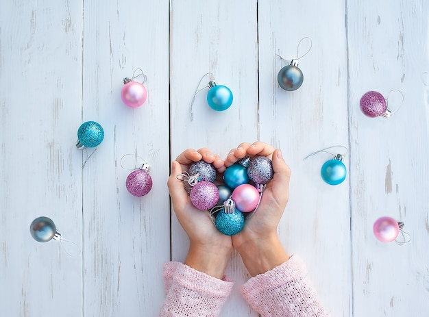 Multicolored cchristmas ornaments in the hands of a girl and on a white wooden table