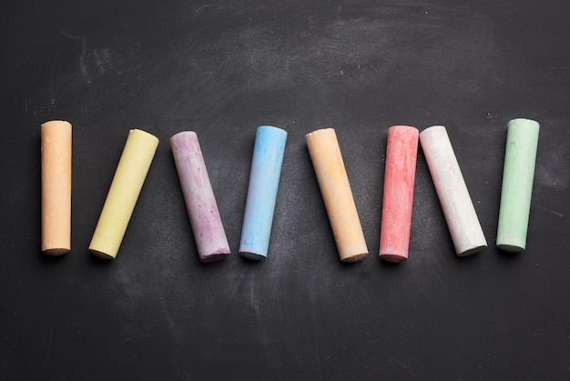Multicolored chalk on lie on empty black chalk board, top view