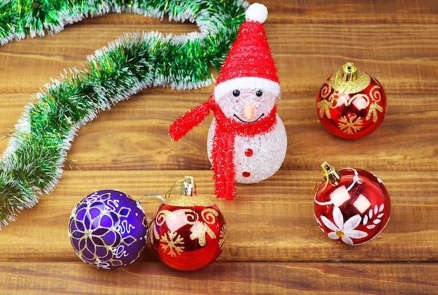 나무 배경에 여러 가지 빛깔된 크리스마스 장난감입니다.