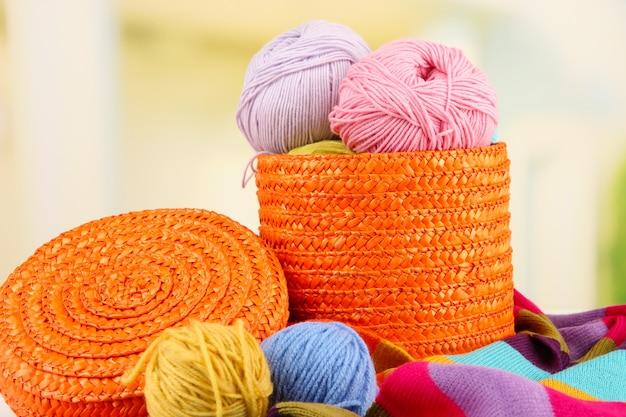 Разноцветные клубки в плетеной корзине с крупным планом яркого шарфа