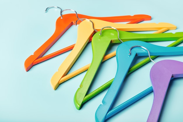 Multicolored clothes hangers isolated on blue