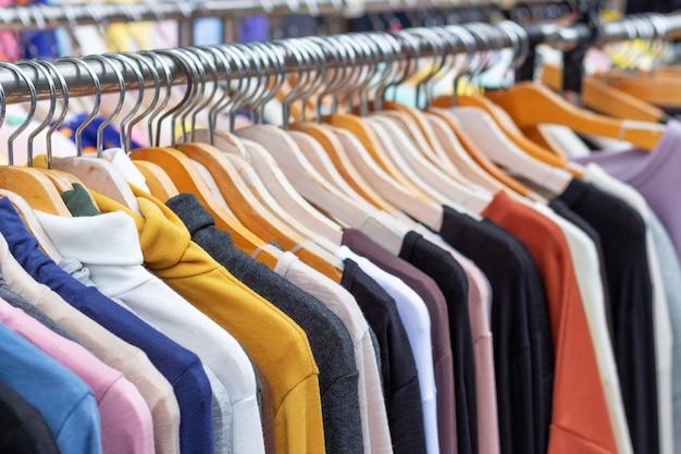 Разноцветная одежда на деревянных вешалках в магазине крупным планом.