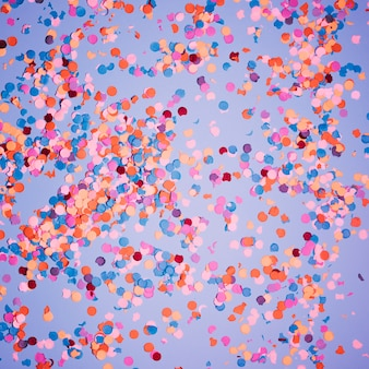 Multicolored confetti over blue backdrop