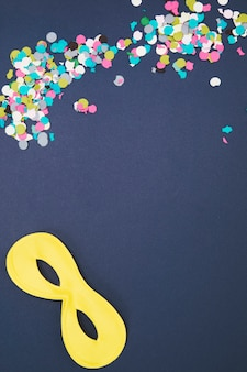 Multicolored confetti with yellow eye mask on colored background