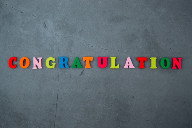 The multicolored congratulation word is made of wooden letters on a grey plastered wall.