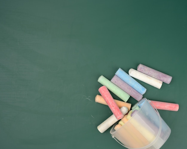 Multicolored crayons on the background of green chalk school blackboard, copy space