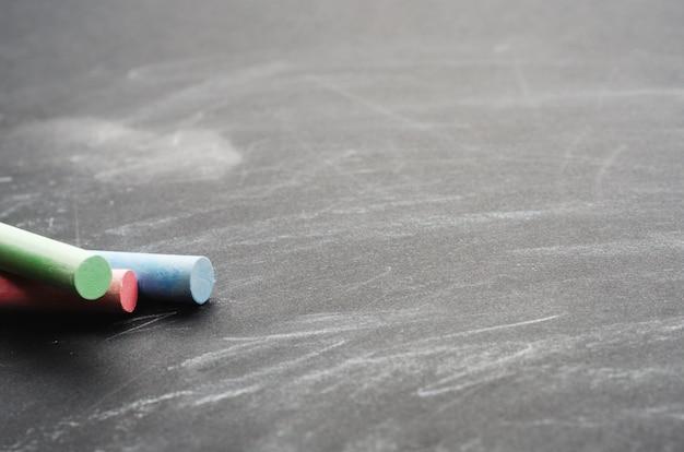 塗られた黒い板に色とりどりのクレヨン。教育委員会、概念的な背景。コピースペース、クローズアップ。