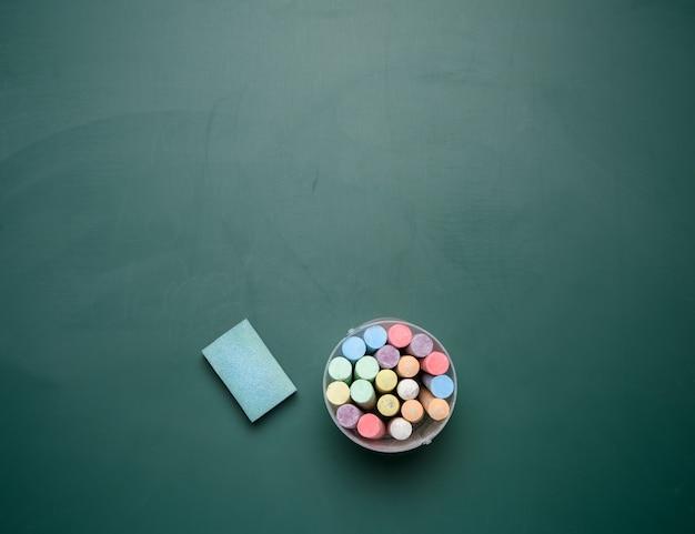 Разноцветные мелки на фоне школьной доски зеленым мелом, копией пространства