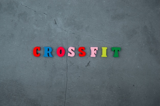 The multicolored crossfit word is made of wooden letters on a grey plastered wall.