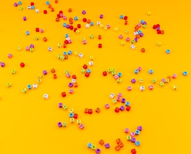 Разноцветные кубики с буквами на желтом фоне