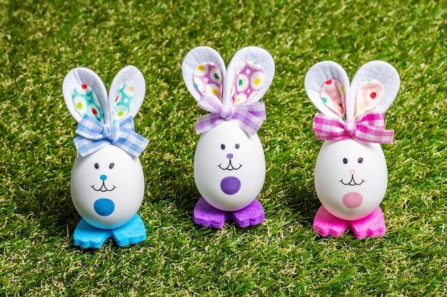Разноцветные милые кролики ручной работы из яиц на зеленой траве