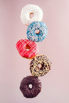Multicolored decorated doughnuts in motion falling