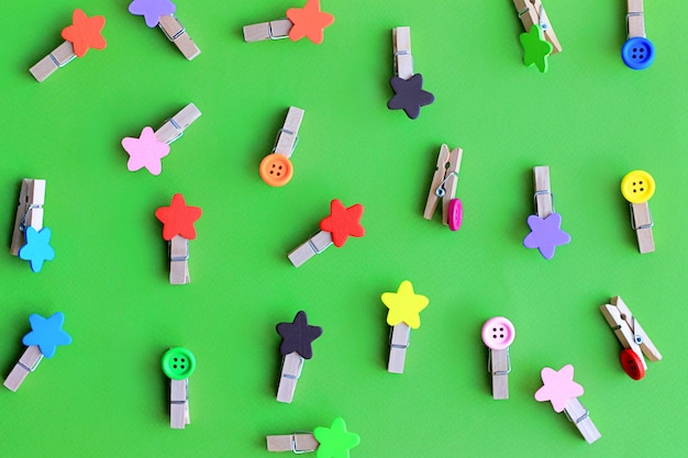 Multicolored decorative clothes pegs for clothes on green background pattern