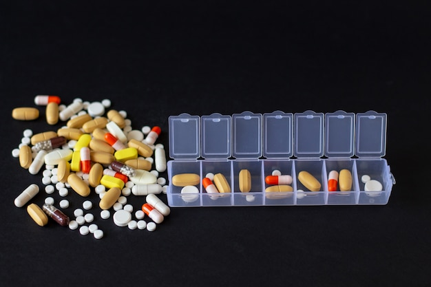 Multicolored different pills with pillbox