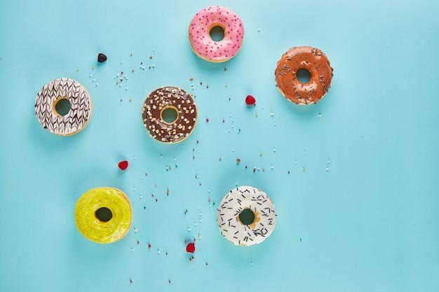 青い背景にフロスティングと振りかける色とりどりのドーナツ。フラットレイ