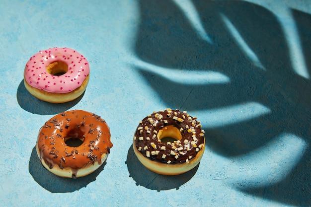 설탕 프로 스 팅과 여러 가지 빛깔 된 도넛, 파란색 배경에 monstera 잎에서 그림자와 뿌리.