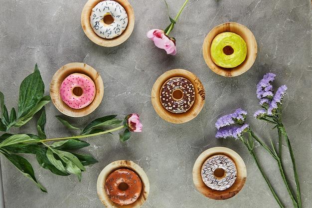釉薬と灰色の背景に花を振りかける色とりどりのドーナツ。フラットレイ