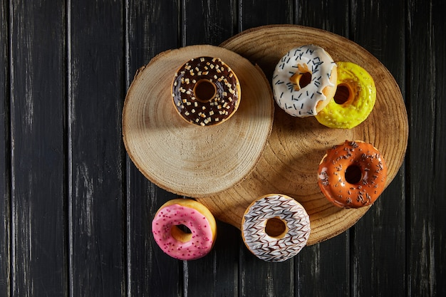 Multicolored donuts with glaze and sprinkles on wooden coasters on a black background. flat lay