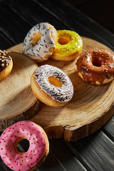 Multicolored donuts with glaze and sprinkles on wooden coasters on a black background.
