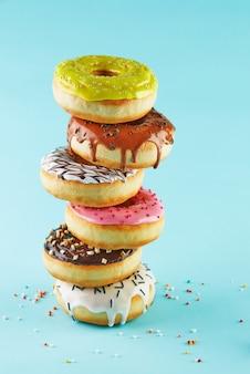 Разноцветные пончики с глазурью и посыпкой уложены стопкой на синем фоне.