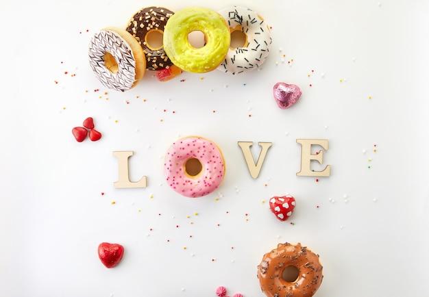 Разноцветные пончики с глазурью, брызгами и любовью надписи на белом фоне. плоская планировка