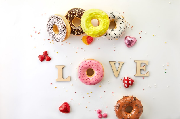 白い背景にアイシング、スプリンクル、碑文の愛を込めた色とりどりのドーナツ。フラットレイ