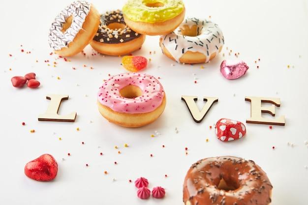 Разноцветные пончики с глазурью, брызгами и любовью надписи на белом фоне.