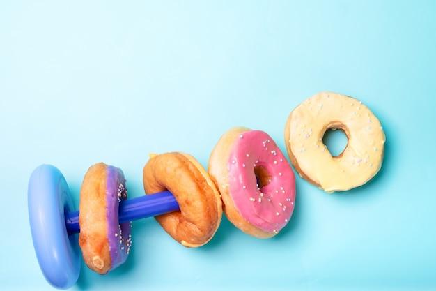 明るい青色の表面に色とりどりのドーナツ