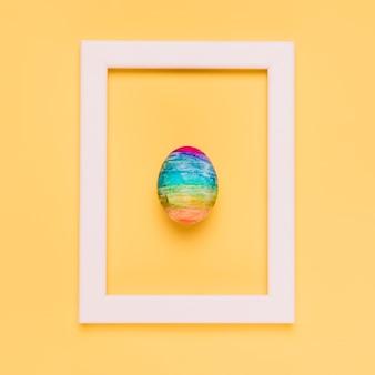 Разноцветное пасхальное яйцо внутри белой рамки на желтом фоне