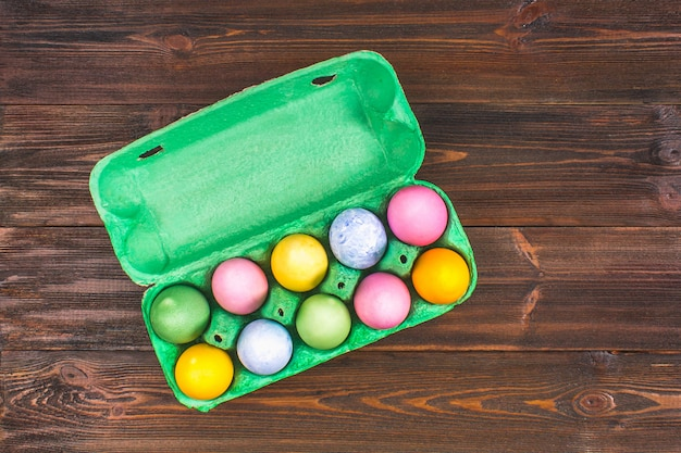 Multicolored easter eggs in a green tray on a brown wooden table.