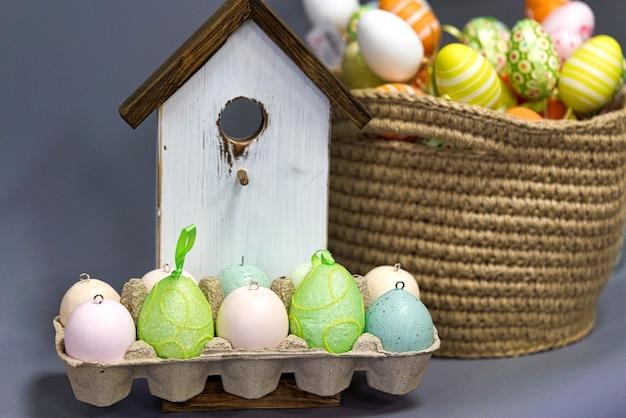 Разноцветные пасхальные яйца на фоне деревянного птичьего домика