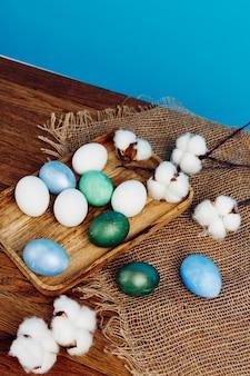 나무 트레이 장식 파란색 배경에 여러 가지 빛깔 된 부활절 달걀.