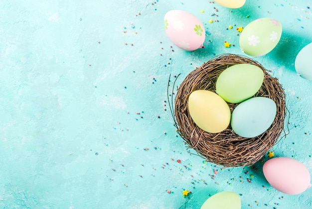 Multicolored easter eggs with decorative bird's nest and sugar sprinkles on a light blue ,