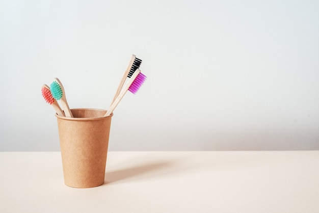 ゼロウェイストコンセプトの持続可能なライフスタイルを備えた紙コップ歯科治療における色とりどりの環境に優しい竹歯ブラシ