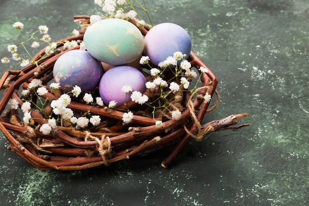Multicolored eggs for easter in nest with flowers on green background. copy space. food background
