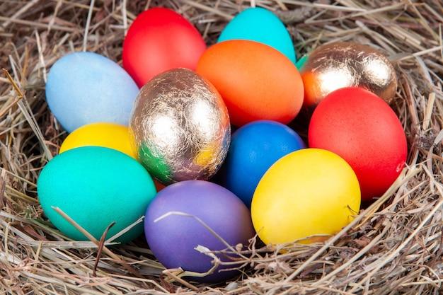 Разноцветные яйца в гнезде в сене. концепция пасхи.