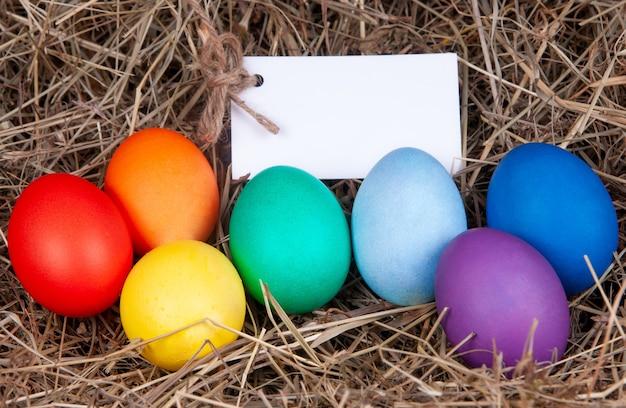 干し草にメモが入った色とりどりの卵。モックアップ、コンセプトイースター。