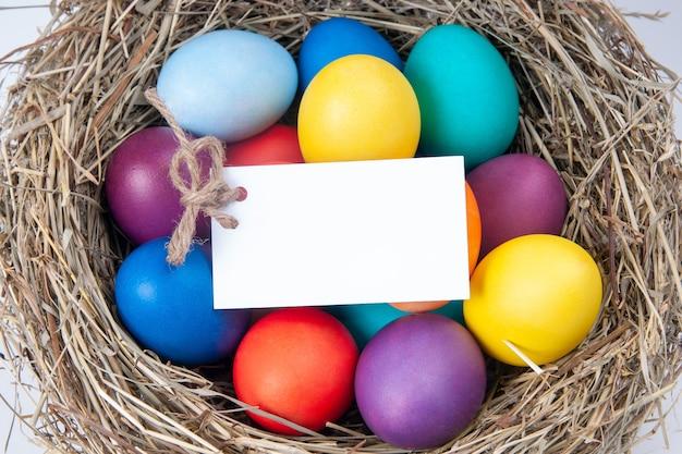 Разноцветные яйца с запиской в сене. макет, концепция пасхи.