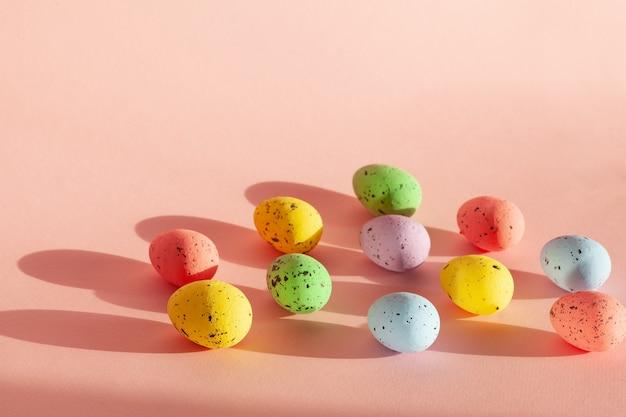 朝日が差し込む色とりどりの卵。ピンクの背景にカラフルな構図。イースターのコンセプト。