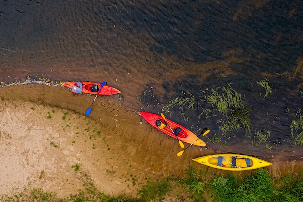 Multicolored empty kayaks and canoes on the riverbank