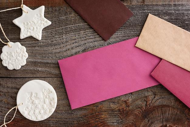 여러 가지 빛깔의 봉투와 나무 배경에 크리스마스 장식. 통신의 개념입니다.