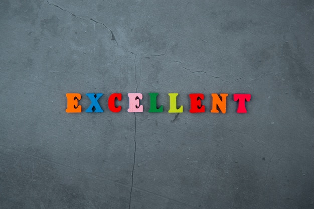 The multicolored excellent word is made of wooden letters on a grey plastered wall