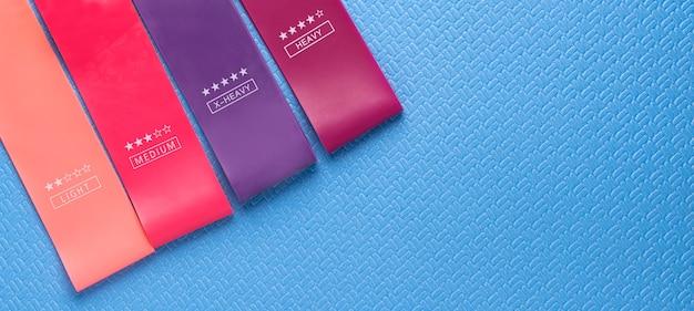 Разноцветные упражнения резинкой фитнес на синем фоне