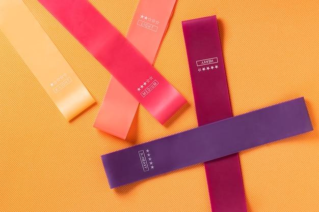 Разноцветные упражнения резинкой фитнес на оранжевом фоне
