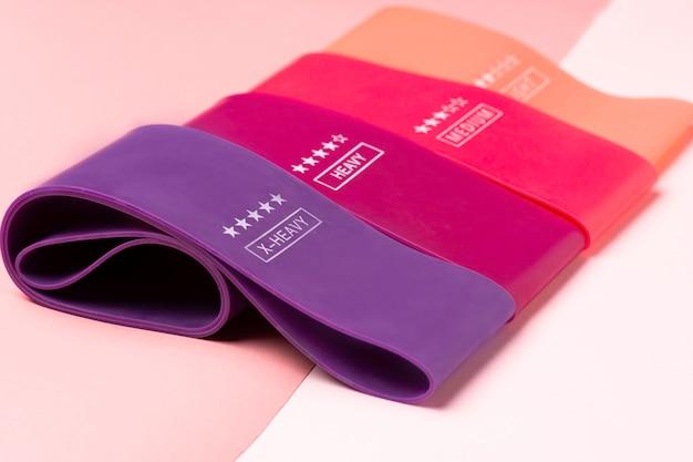 Разноцветные упражнения резинкой фитнес на розовом фоне